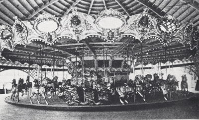 "In this factory photograph showing the carousel newly installed at Carsonia Park for the 1923 season, the carousel is rotated to reveal one of a pair of dragon chariots. ""Pan"" has taken the lead on this side and is seen to the right of the chariot. Photograph from the Passing Scene Series by George M. Meiser, IX and Gloria Jean Meiser."