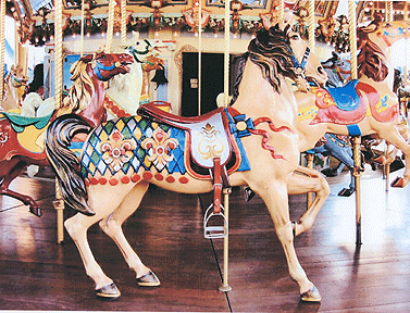 "This outer row standing horse with fleur de lis ornamented trappings is what is known to carousel historians and carving collectors as a ""thoroughbred."" Dentzel carousels typically had four to six of these majestic horses on the outer row. This horse has been named, Tony, and can be seen immediately standing in place in front of the chariot on one of the photographs of the carousel in Carsonia Park. Photograph by Chris K. Benson, courtesy of the National Carousel Association"