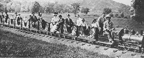 """In this 1902 photograph, """"The Little Train"""" one of Carsonia's most popular and enduring attractions, is shown chugging along its 1900-foot course between the theatre and Carsonia Inn. Fare for the round trip was a nickel. As no round table existed , the train returned to the station in reverse. In an effort to generate interest in the railway, its operators offered a $100.00 building lot in Rosedale (Laureldale) to the person taking the most train rides during the summer of 1903."""