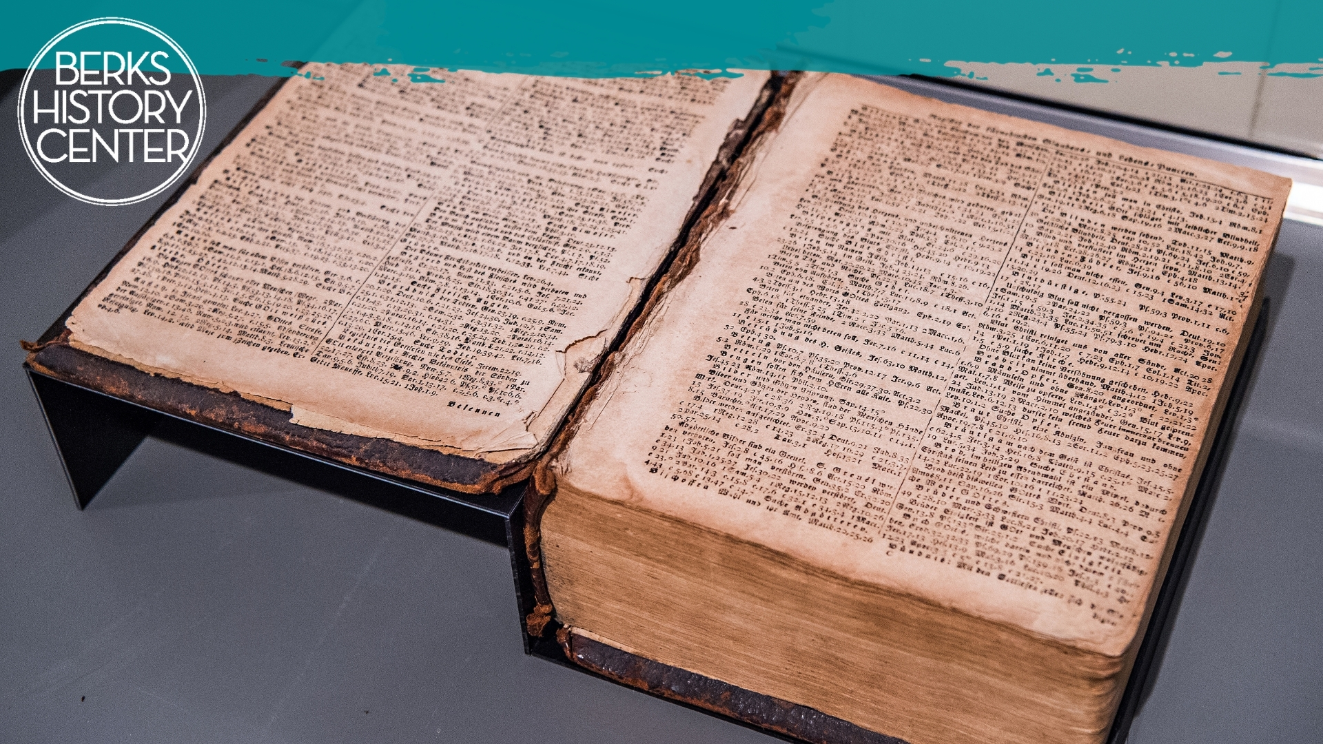 """Collection image of an open book, """"Gottlob Jungman Bible, 1805"""" with white circle Berks History Center logo and 'BHC Blue' paint stripe along top."""