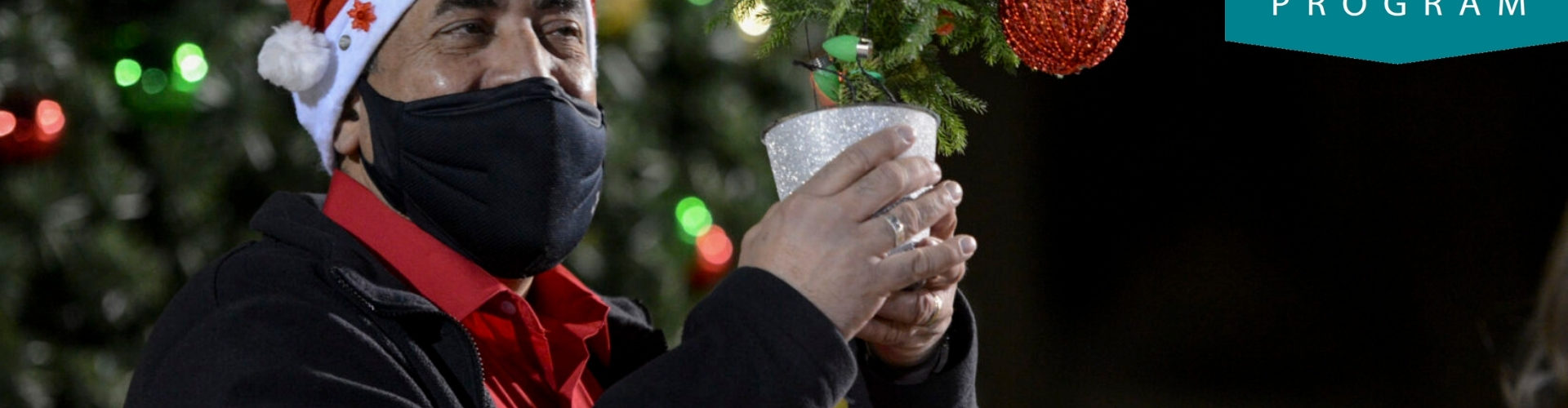 Man in black mask and Santa hat holding up a small, lighted christmas tree in a silver glitter cup, with a single, large red ornament, overlaid with a 'BHC Blue' paint stripe at the bottom and the Berks History Center 2nd Saturday emblem logo